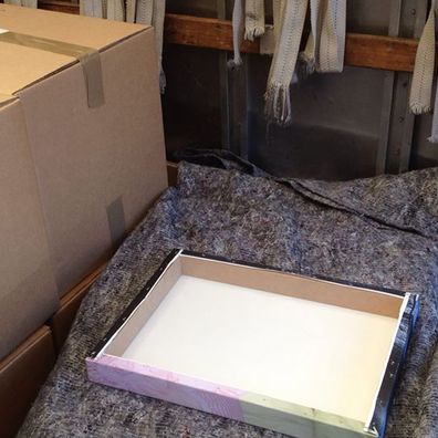 Canvas paintings being securely packaged in the back of the removal truck